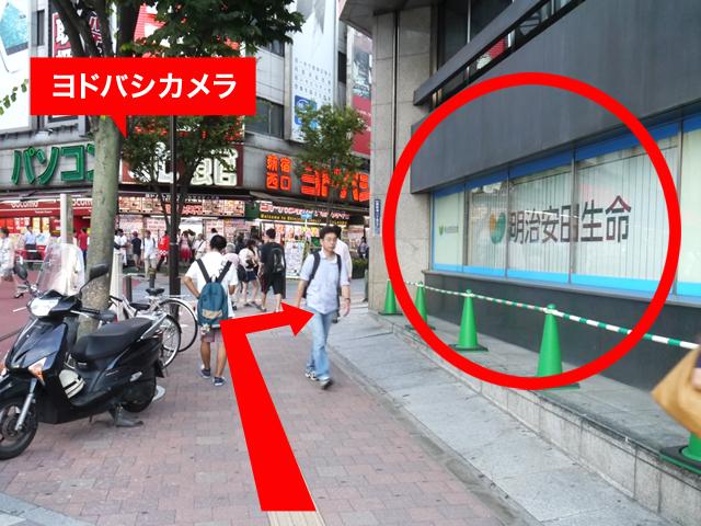 右手にある「明治安田生命新宿ビル」に沿って進んでください。
