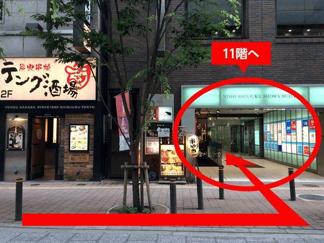 向かい側の「炭火串焼テング酒場」が見えたら、その右手にある「西新宿昭和ビル(NISHI‐SHINJUKU SHOWA BUILDING)」の11階です。